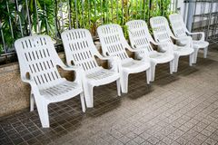 Row of white plastic outdoor chairs with backrest by swimming po. Ol on brown mosaic tile floor against metal rails Royalty Free Stock Images