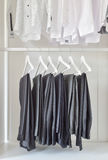 Row of white shirts and black pants hanging in wooden wardrobe Stock Image