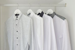 Row of white shirts hanging  in wooden wardrobe Royalty Free Stock Photo