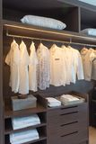 Row of white shirts on rail. In wooden closet, interior design concept stock image