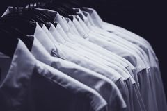 Row of white shirts. Hang on hangers in the darkness of a wardrobe, toned in blue royalty free stock photography