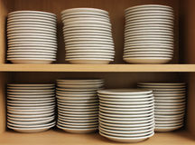 A Row White Tableware sat on a shelf. A Row of White tableware, cups, saucers and plates sat on a shelf Royalty Free Stock Images