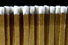 Row of white tipped matches. Row of paper matches with white tips background texture isolated on a black background Stock Image