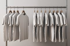 Row of white tshirts. On hangers. Concrete wall background. Style and design concept. 3D Rendering stock illustration