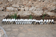 Row of white wooden clogs. Row of wooden clogs leaning against wall outdoors Stock Images
