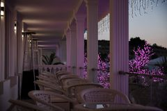 Row of wicker furniture on the balcony in the late evening stock images