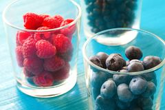 Row of wild berries in bowls on wooden background Royalty Free Stock Photo