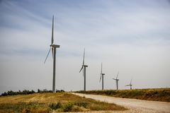 A row of wind generators. On a field with a rural road Royalty Free Stock Image