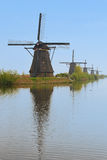 A row of windmill from front to back in kinderdijk with beautiful river water reflection in vertical view Stock Images