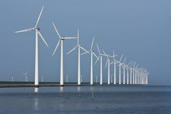 Row of windmills, mirrored in the Dutch sea Royalty Free Stock Photography
