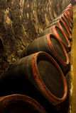 Row of Wine barrels in winery cellar recedes into. Row of Old wine barrels are stored in winery cellar near aged wall resedes into the distance royalty free stock image