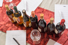 Row of Wine Bottles with Glasses and Tasting Forms Stock Images