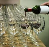 row of wine glasses and a bottle of red wine. stock image