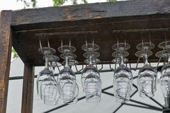 Row of wine glasses, hanging on a terrace rack. Royalty Free Stock Photography