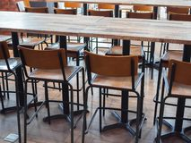 Row of wooden bar stools and wooden table royalty free stock photography