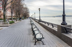 Row of Wooden Benches on a Riverside Footpath Stock Images
