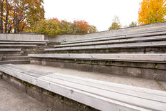 Row of wooden benches at summer theater in a city park Royalty Free Stock Image