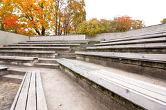 Row of wooden benches at summer theater in a city park Royalty Free Stock Photography
