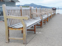 Row of wooden benches of wharf Stock Photo