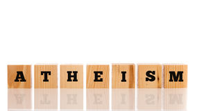 Row of wooden blocks spelling - Atheism. Signifying a disbelief or rejection of God, often leading to paganism and heathenism, on a white reflective surface Stock Image