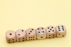 Row of wooden dice. Row of many wooden dice on a yellow background Stock Photo
