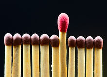 Row of wooden matches with one putted out.  Royalty Free Stock Photo
