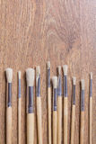 Row of wooden paint brushes on table background Royalty Free Stock Photo