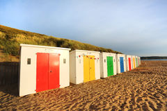 Row of wooden painted brightly coloured beach huts Stock Photos