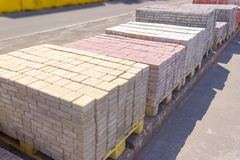Varicolored concrete decorative pavement tiles on an outdoor war. Row of a wooden pallets with concrete decorative pavement tiles rectangular shape and different stock images