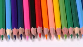 Row of wooden pencils. Colorful pencils of different colours and shades lying in line on whote surface, slowly moving along row, sharp ends, art. Close up, 4K stock footage