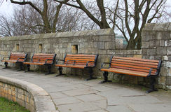A row of wooden seats. On the city of York ramparts, UK Royalty Free Stock Photography