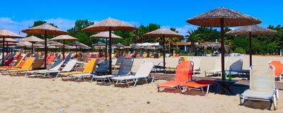 Row of wooden umbrellas at sandy beach. Row of wooden umbrellas and deck chair at sandy beach bar, sea and blue sky vacation banner background, Greece Stock Photos