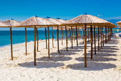 Row of wooden umbrellas at sandy beach, sea and blue sky Royalty Free Stock Photography