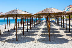 Row of wooden umbrellas at sandy beach, sea and blue sky Royalty Free Stock Photo
