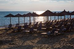Row of wooden umbrellas at sandy beach, sea during the sunset Royalty Free Stock Photography