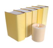 Row of yellow books with a candle Stock Images