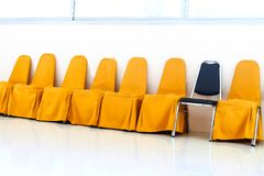 A row of yellow chairs and blue chair Stock Photo