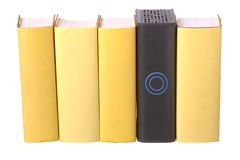 Row of yellow hardback books with a computer hard. Drive isolated on a white background royalty free stock photography