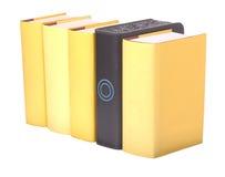 Row of yellow hardback books with a computer hard Stock Photos