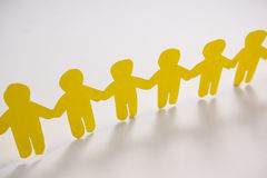 Row of yellow paper cut-out figures. On white background Royalty Free Stock Image