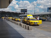 Row of yellow taxis waiting in front of the airport Stock Photos