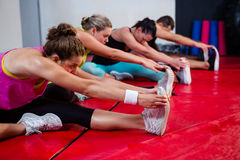 Row of young athletes practicing stretch exercise royalty free stock photos