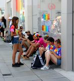 Young people using mobiles at Brighton Pride Festival. Row of young people sat using mobile phones in street during Brighton Pride festival, England royalty free stock photos