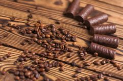 Row of yummy chocolate candies and scattered fried halves of coffee beans. On old weathered wooden table stock image