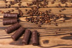 Row of yummy chocolate candies and scattered fried halves of coffee beans. On old weathered wooden table royalty free stock photos