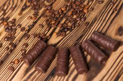 Row of yummy chocolate candies and scattered fried halves of coffee beans. On old weathered wooden table stock images