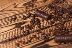 Row of yummy chocolate candies and scattered fried halves of coffee beans. On old weathered wooden table. With copy space royalty free stock photos