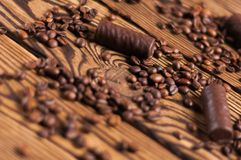 Row of yummy chocolate candies and scattered fried halves of coffee beans. On old weathered wooden table royalty free stock image