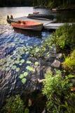 Rowboat στην ακτή λιμνών στο σούρουπο Στοκ Φωτογραφία