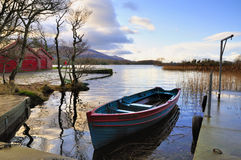 Rowboat. Small boat at anchor at Killarney, Co.Kerry, Ireland,showing red boathouse on left of picture Stock Photo